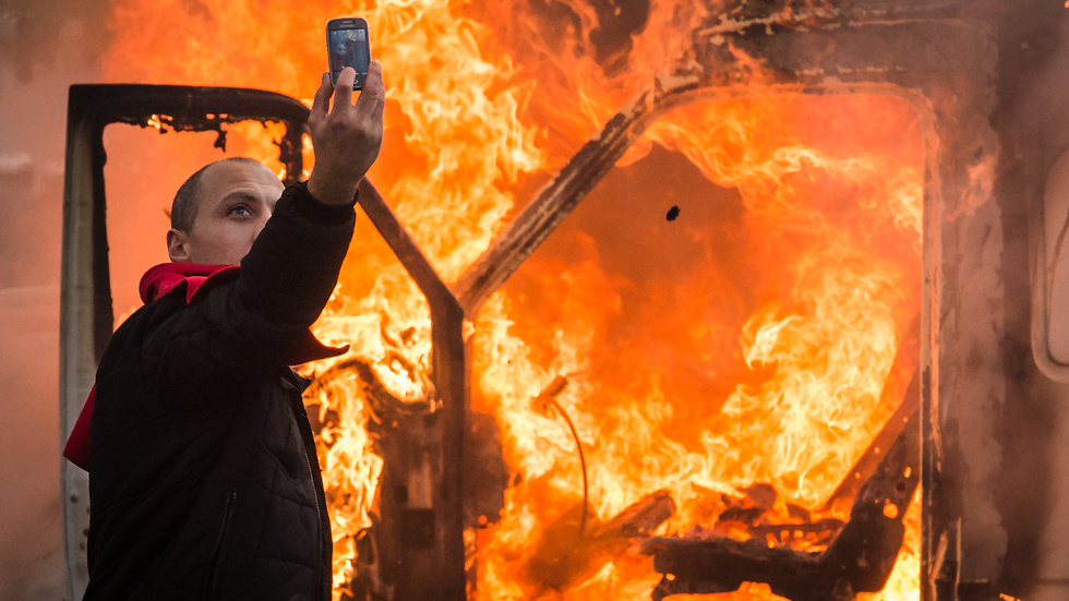 En demonstrant tar en selfie framför en brinnande bil under en demonstration i Bryssel i november.
