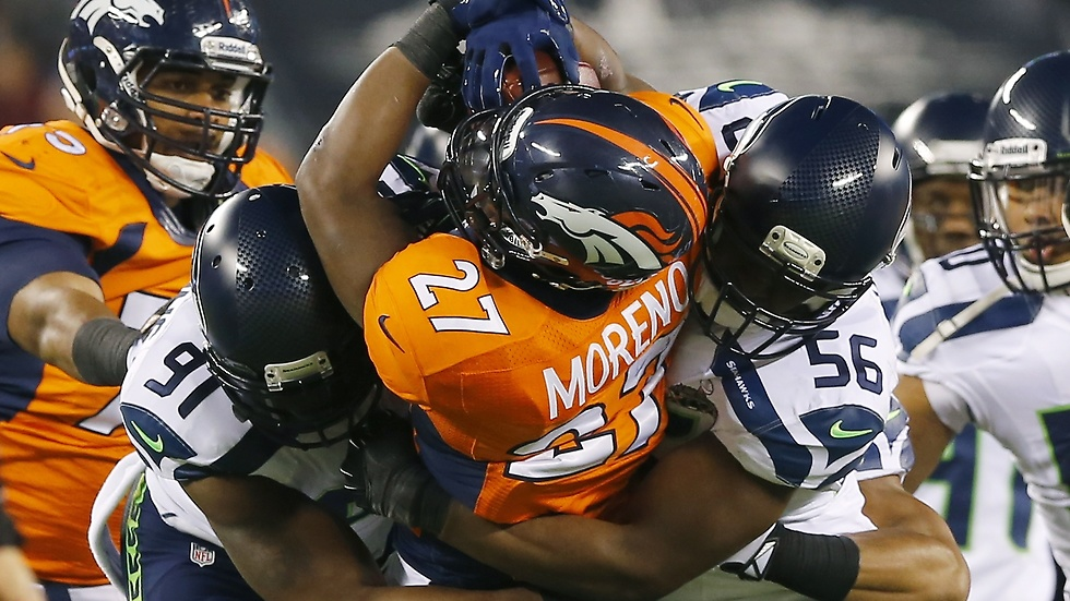 Knowshon Moreno tacklas av Chris Clemons och Cliff Avril.